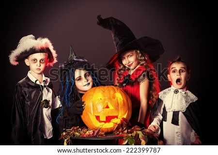 Cheerful children in halloween costumes posing with pumpkin over dark background. - stock photo