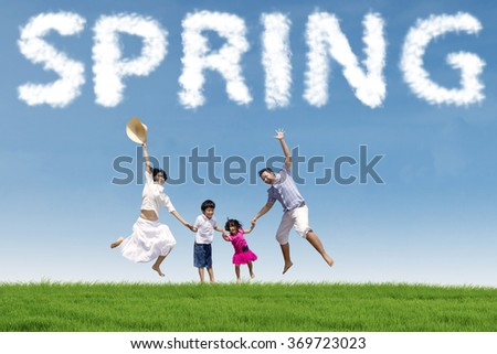 Cheerful children playing on the meadow with their parents and jumping together under a spring cloud - stock photo