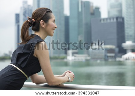 Cheerful Chinese business woman standing outside with office buildings in the background. Portrait of an Asian business woman looking away. - stock photo
