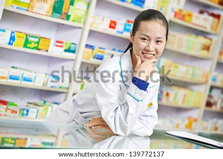 cheerful chinese pharmacist chemist woman standing in china pharmacy drugstore - stock photo