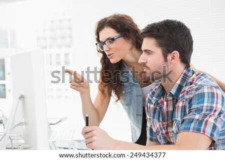 Cheerful colleagues working together with computer in the office - stock photo