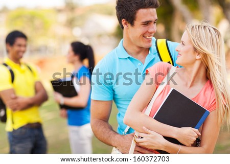 cheerful college couple embracing outdoors - stock photo