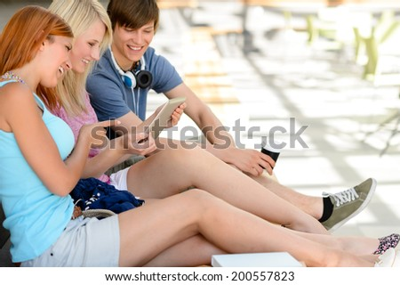Cheerful college student friends using tablet together sitting in assembly hall - stock photo