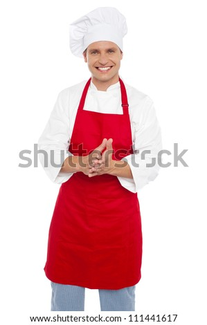 Cheerful confident male chef in proper uniform standing with hands together - stock photo