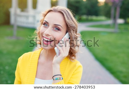 Cheerful conversation. Attractive young woman talking by phone while walking by summer park. - stock photo