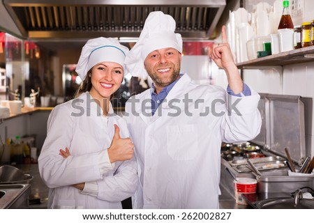 Cheerful cooks working at take-away restaurant kitchen - stock photo