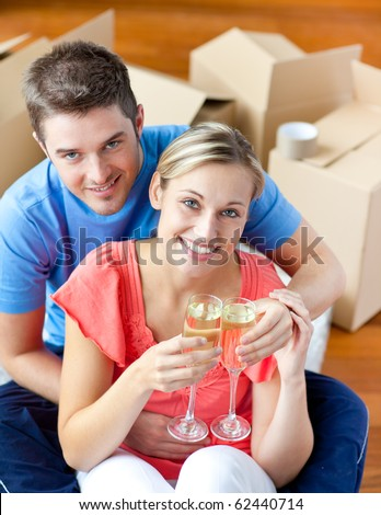 Cheerful couple celebrating their new house with champagne sitting on the floor looking at the camera - stock photo