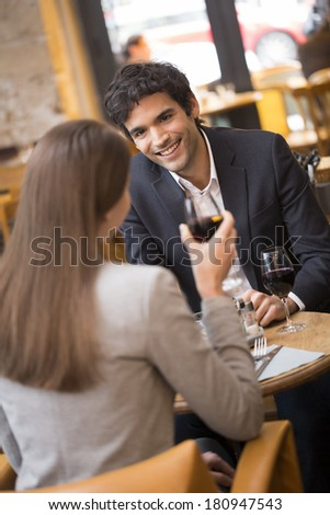 Cheerful couple drinking red wine in French restaurant, focus on man - stock photo