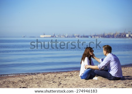 Cheerful couple embracing and posing on the beach on a sunny day. Picture (photo) of a happy couple having fun on the beach, listen music by phone. Hipster style. Outdoor shot - stock photo