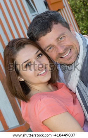 Cheerful couple embracing in front of house - Love and happiness - stock photo