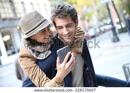 Cheerful couple having fun playing with smartphone - stock photo