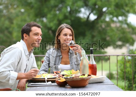 Cheerful couple having lunch in hotel garden - stock photo