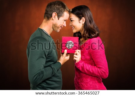 Cheerful couple holding gift box against shades of brown - stock photo