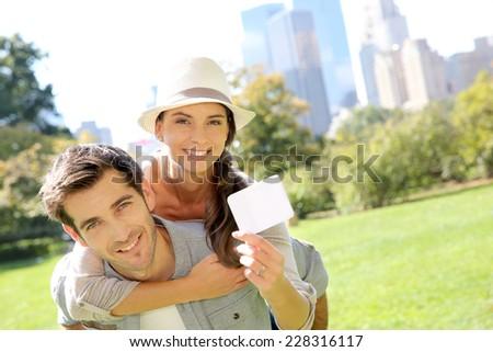 Cheerful couple holding tourits pass of New York City - stock photo