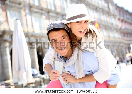 Cheerful couple holding visitor pass of Madrid capital - stock photo