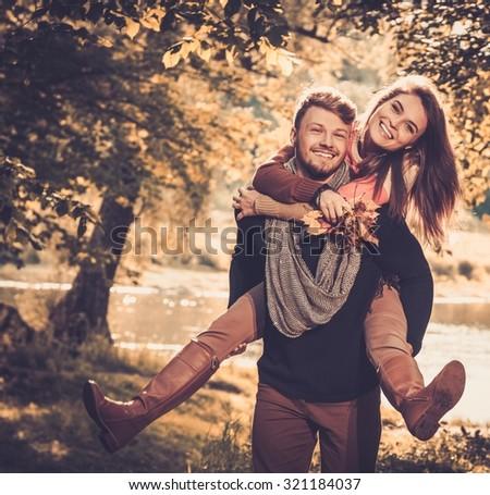 Cheerful couple in autumn park having fun - stock photo