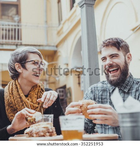 Cheerful Couple In Fast Food Reastaurant Eating Burgers - stock photo