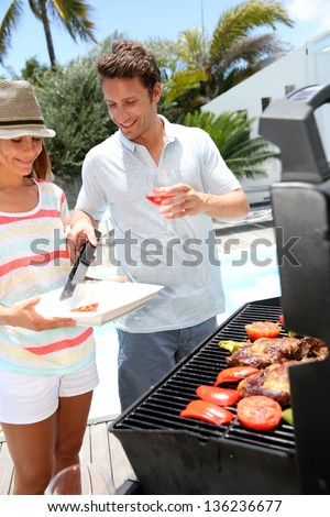 Cheerful couple in holidays preparing grilled meat - stock photo