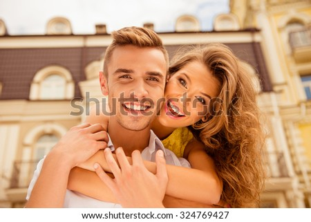 Cheerful couple in love on the background of buildings - stock photo