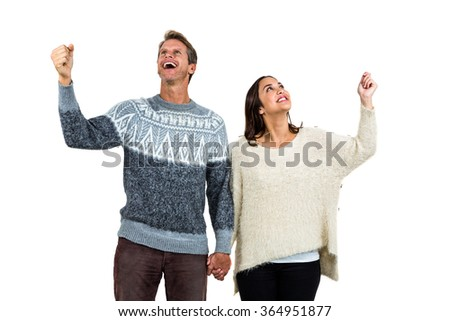 Cheerful couple in warm clothing gesturing against white background - stock photo