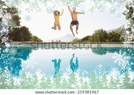 Cheerful couple jumping into swimming pool against snow - stock photo
