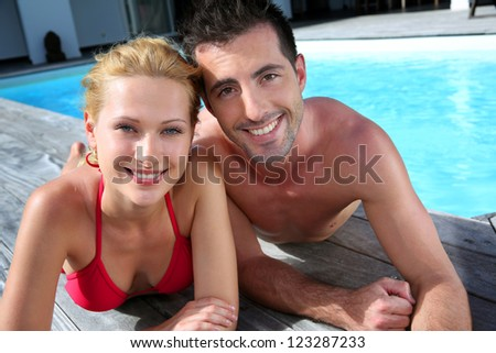 Cheerful couple laying on pool deck in front of house - stock photo
