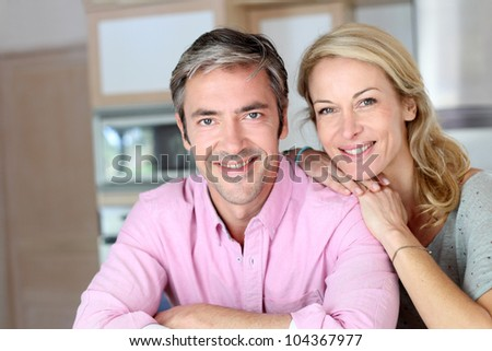 Cheerful couple leaning on kitchen counter - stock photo