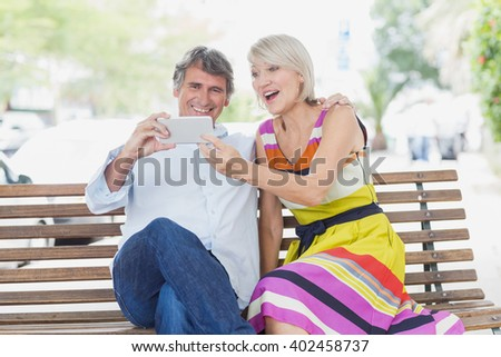 Cheerful couple looking at mobile phone sitting on bench - stock photo