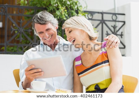 Cheerful couple looking at tablet computer while sitting in cafe - stock photo