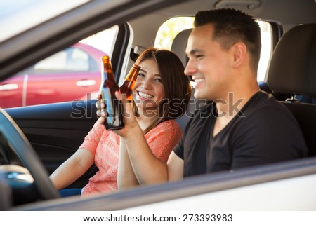 Cheerful couple of Hispanic young adults drinking beers while driving a car - stock photo