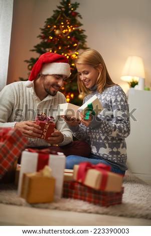 Cheerful couple opening giftboxes on Christmas night - stock photo