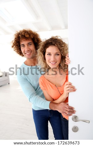 Cheerful couple opening new home entrance door - stock photo