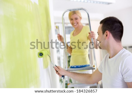 Cheerful couple  painting wall in their new house - stock photo