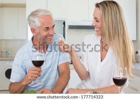 Cheerful couple preparing dinner together and drinking red wine at home in the kitchen - stock photo