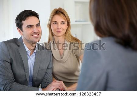 Cheerful couple receiving good news from advisor - stock photo