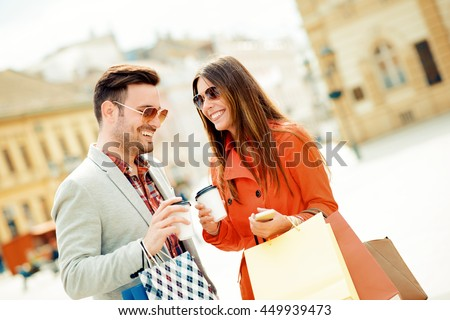 Cheerful couple shopping together in the city. - stock photo