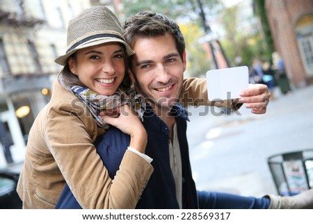 Cheerful couple showing New York City pass - stock photo