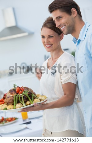 Cheerful couple showing roast chicken in the kitchen to the camera - stock photo