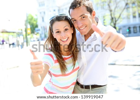 Cheerful couple showing thumbs up - stock photo