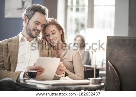 cheerful couple sitting in a cafe and using a digital tablet - stock photo