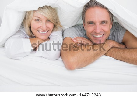 Cheerful couple smiling under the covers at the camera at home in bed - stock photo