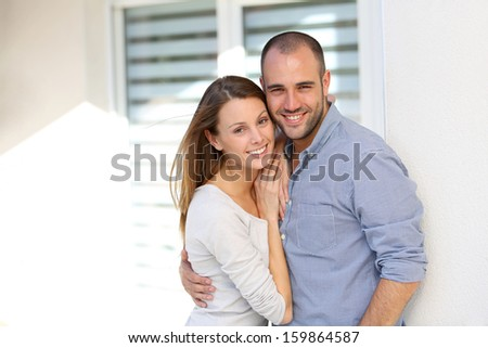 Cheerful couple standing in front of home - stock photo