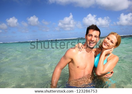 Cheerful couple swimming in a caribbean lagoon - stock photo