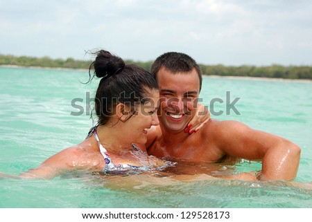 Cheerful couple swimming in the ocean - stock photo