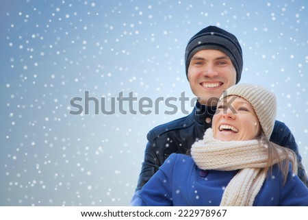 Cheerful couple together under winter snow falling - stock photo