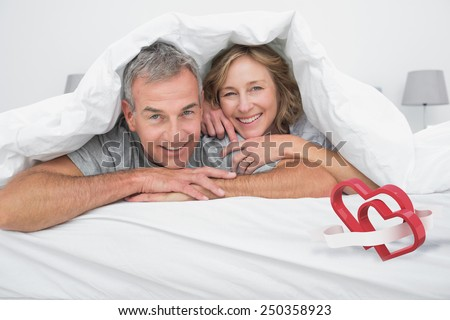 Cheerful couple under the duvet against linking hearts - stock photo