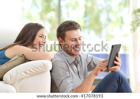Cheerful couple using a tablet on line sitting in the living room at home with a window in the background - stock photo