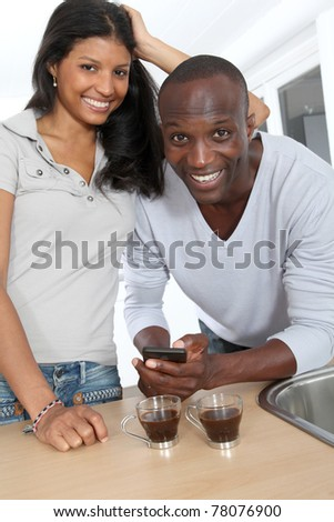 Cheerful couple using smartphone while taking coffee - stock photo