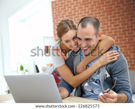 Cheerful couple websurfing on internet with laptop - stock photo