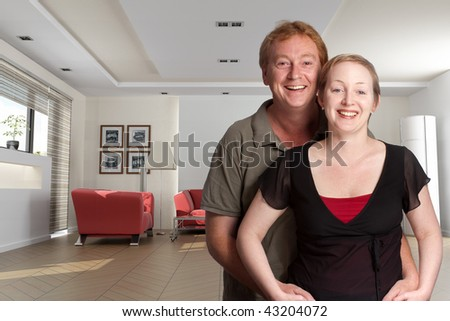 Cheerful couple with a living room as background - stock photo